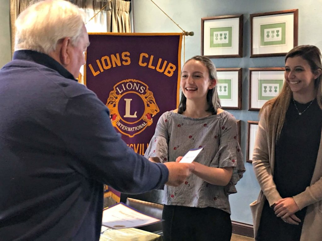 Lion Dennis Steed presents Student of the Month certificates to Sarah Naatz, middle, and Madelyn Byrne.